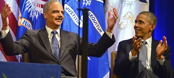 Attorney General Holder claps in surprise as U.S. President Obama applauds at the announcement that Aretha Franklin would entertain at the unveiling of Holder's official portrait in Washington
